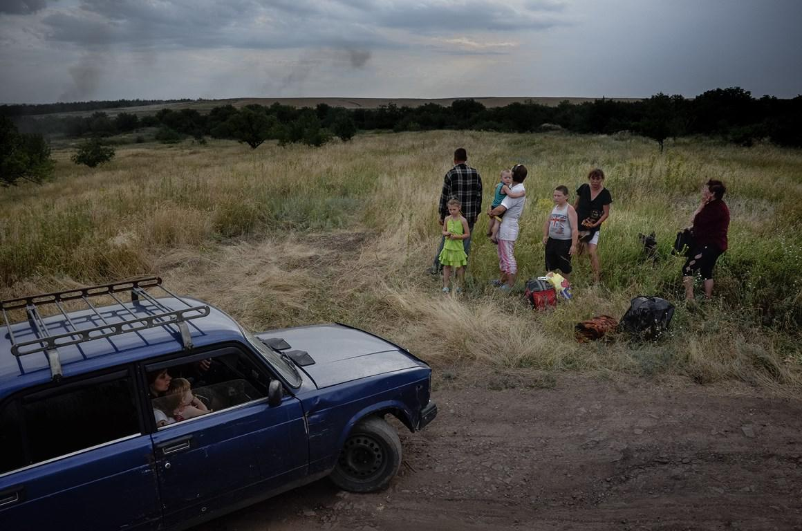 Local people seen in the field at the Russian territory near the city of Donetsk waiting during the shelling of their village Uralo-Kavkaz, Eastern Ukraine.