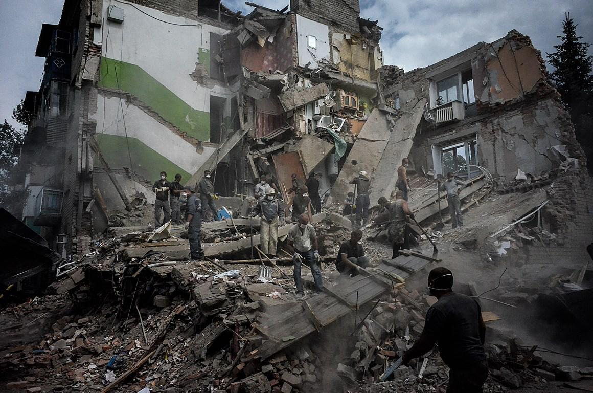 Local people and rescue teams remove debris in a collapsed apartment building after an airstrike on July, 15th in the city of Snezhnoe, Eastern Ukraine.