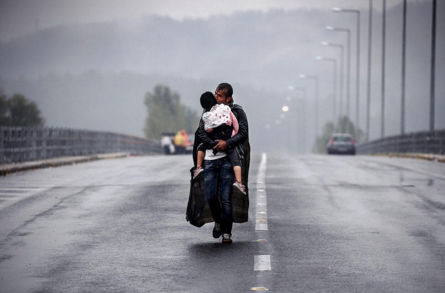 Un réfugié syrien embrasse sa fille pendant qu'il marche à travers la plus torrentielle en direction de la frontière gréco-macédonienne, à proximité du village d'Idomeni - 10 septembre 2015 - REUTERS/Yannis Behrakis