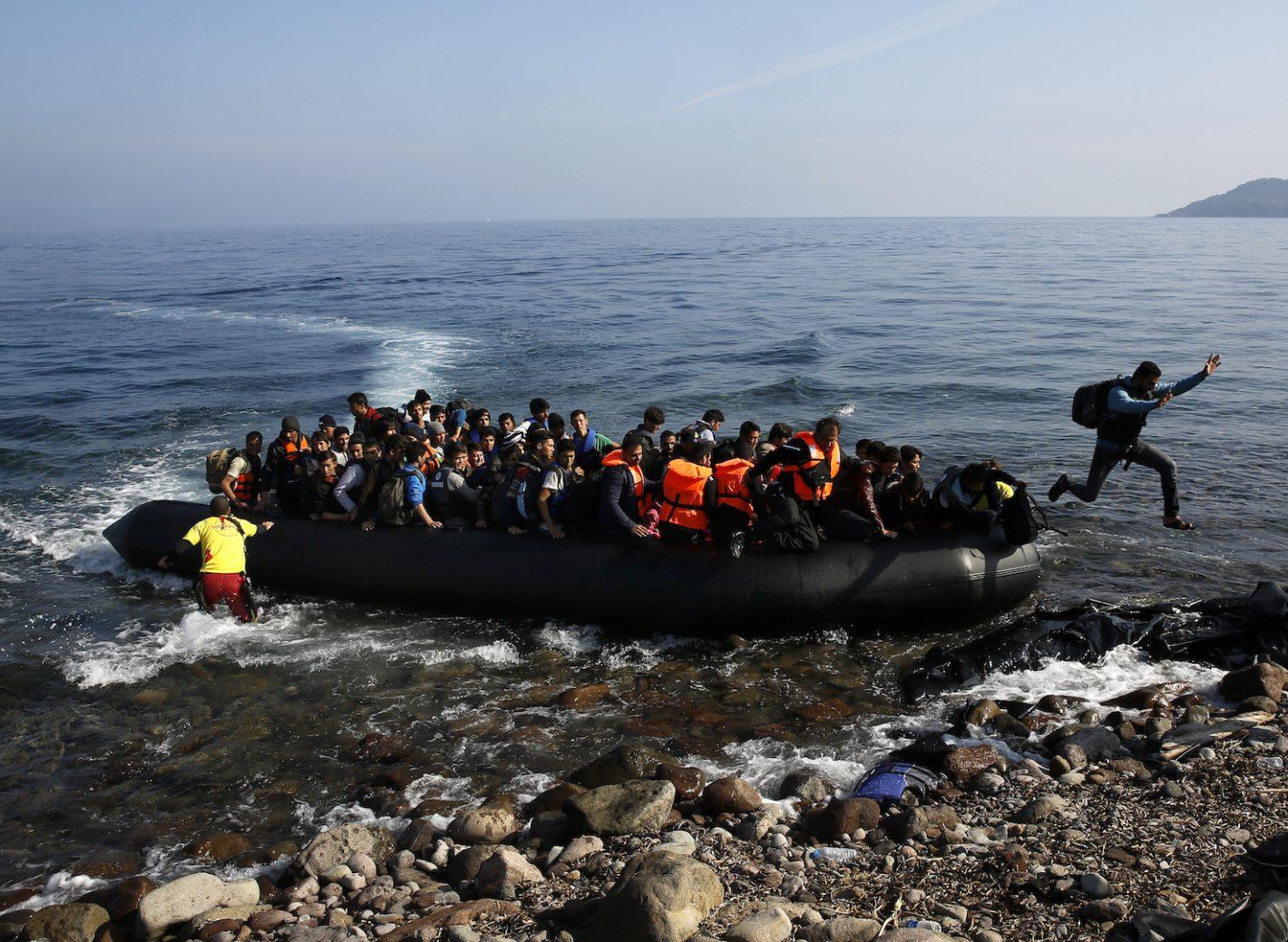 Un migrant Afghan saute d'un radeau bondé sur une plage de l'île grecque de Lesbos, après une traversée depuis la côte turque. 19 octobre 2015 - REUTERS/Yannis Behrakis