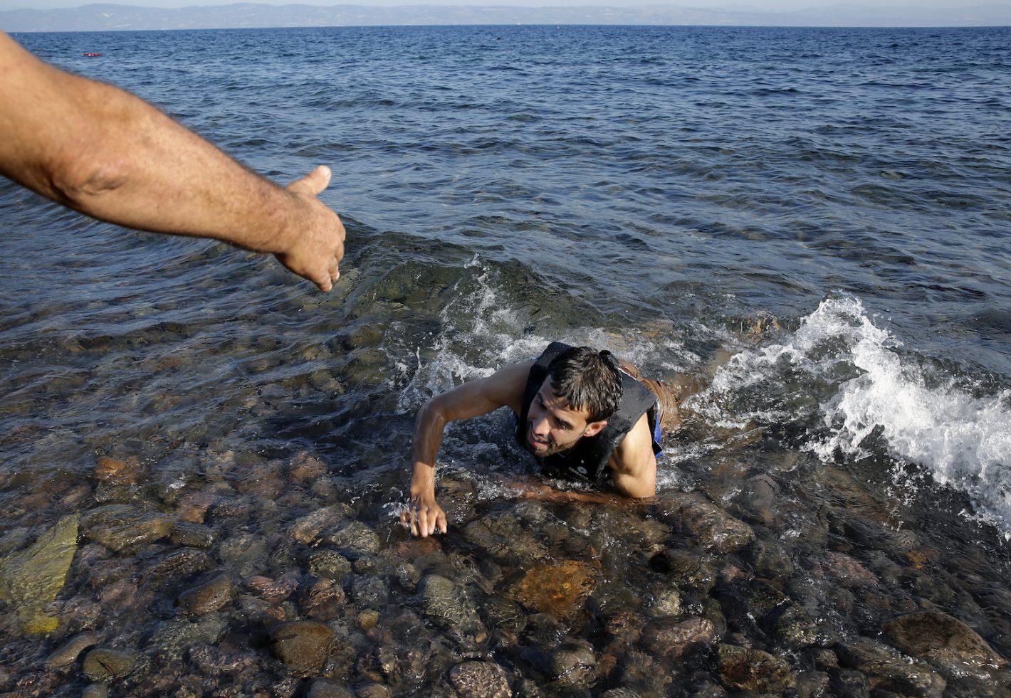 Un habitant de l'île grecque de Lesbos tend la main à un réfugié Syrien épuisé qui vient de tomber d'un canot de migrants surpeuplé. 17 septembre 2015 - REUTERS/Yannis Behrakis