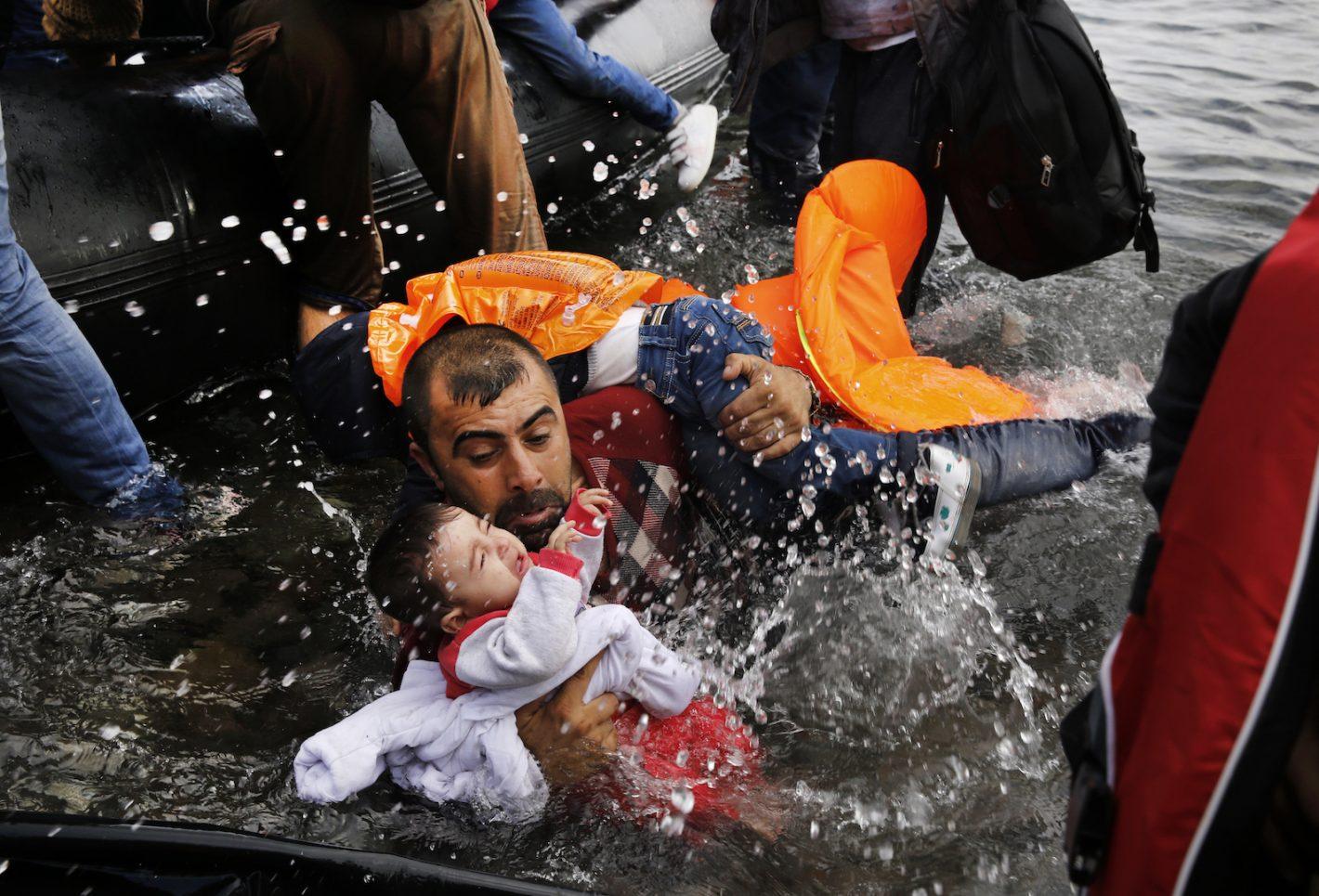 Un réfugié syrien soutient ses deux enfants et lutte pour débarquer d'un canot sur la côte Nord de l'île grecque de Lesbos, après avoir traversé la Mer Egée depuis la Turquie. Plus de 850 000 migrants et réfugiés sont arrivés dans les îles grecques en 2015. 24 septembre 2015 - REUTERS/Yannis Behrakis