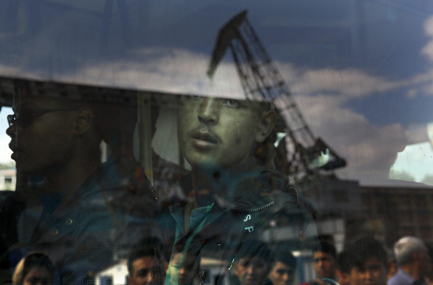 Un migrant Afghan vu à l'intérieur d'un bus au Port de Pirée, près d'Athènes, après son arrivée par le Ferry Eleftherios Venizelos avec plus de 2500 migrants et réfugiés en provenance de l'île de Lesbos. 8 octobre 2015 - REUTERS/Yannis Behrakis