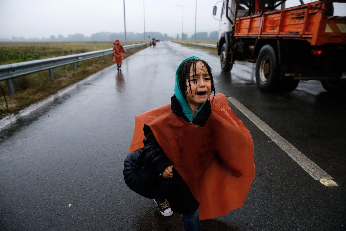 Une jeune réfugiée syrienne, brièvement séparée de ses parents, pleure alors qu'elle marche en direction de la frontière gréco-macédonienne, à proximité du village grec d'Idomeni. Elle fait partie des 7000 réfugiés et migrants, individus isolés ou famille avec enfants arrivés à pied, par trains, bus ou taxis, laissés à leur sort après avoir passé la nuit dehors sous une pluie torrentielle à la frontière gréco-macédonienne. La police macédonienne a imposé un rationnement dans le flux des réfugiés. 10 Septembre 2015 - REUTERS/Yannis Behrakis