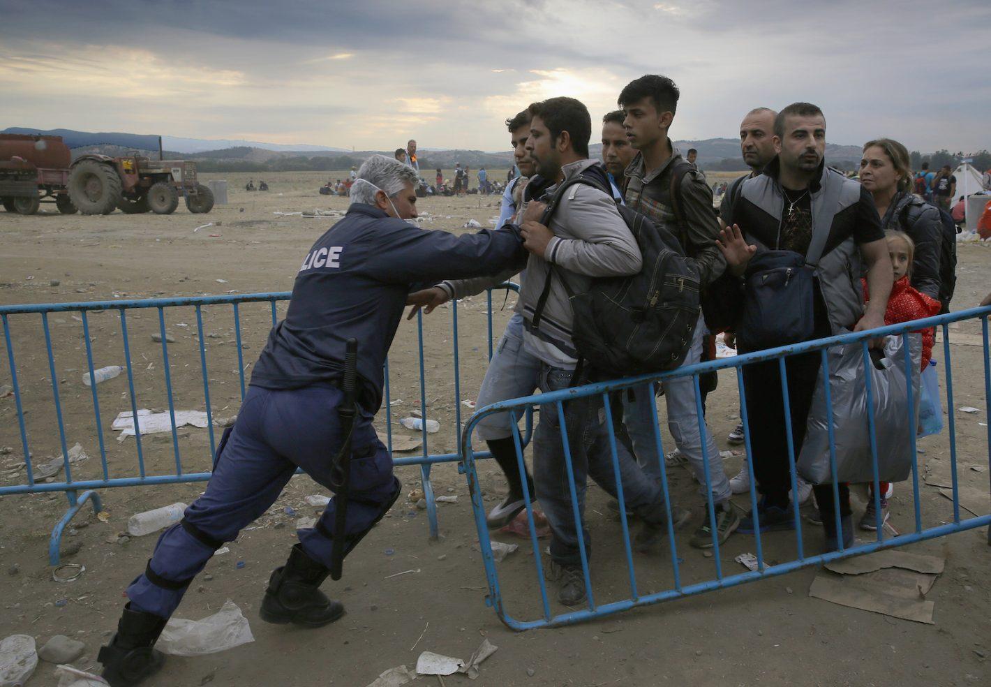 Un policier grec repousse des réfugiés derrière une barrière - Frontière gréco-macédonienne / village d'Idomeni. Des milliers de réfugiés et de migrants attendent pour traverser la frontière. 9 septembre 2015 - REUTERS/Yannis Behrakis