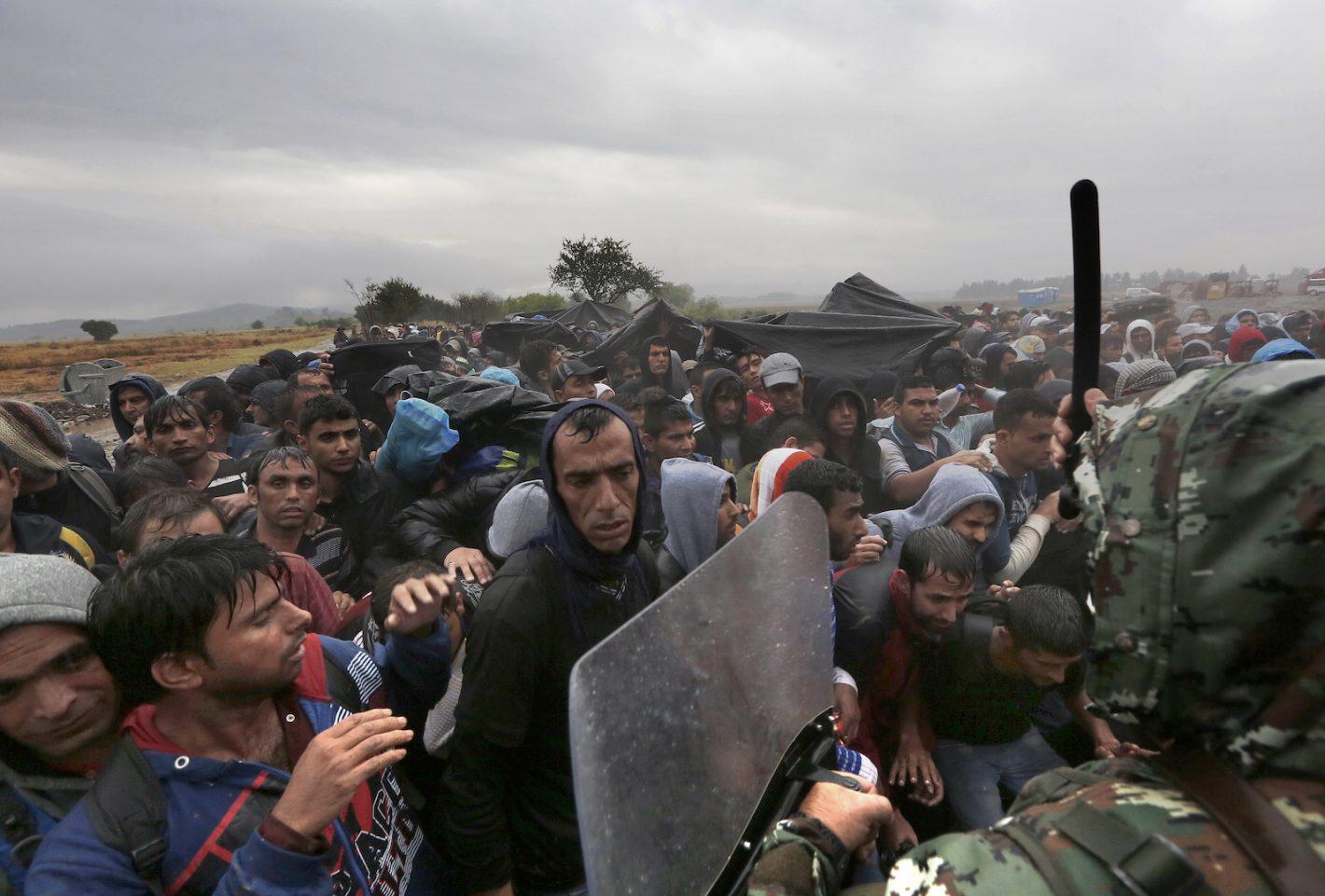 Un policier macédonien lève son bâton contre les réfugiés et les migrants bloqués à la frontière gréco-macédonienne - village d'Idomeni - 10 Septembre 2015. REUTERS / Yannis Behrakis