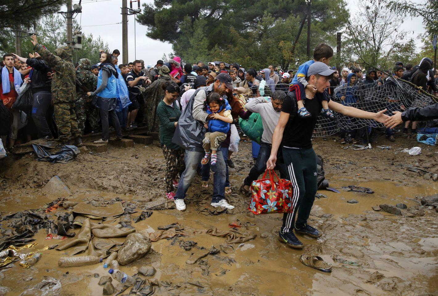 Des réfugiés syriens marchent à travers la boue pour traverser la frontière gréco-macédonienne / village d'Idomeni - 10 septembre 2015 - REUTERS/Yannis Behrakis