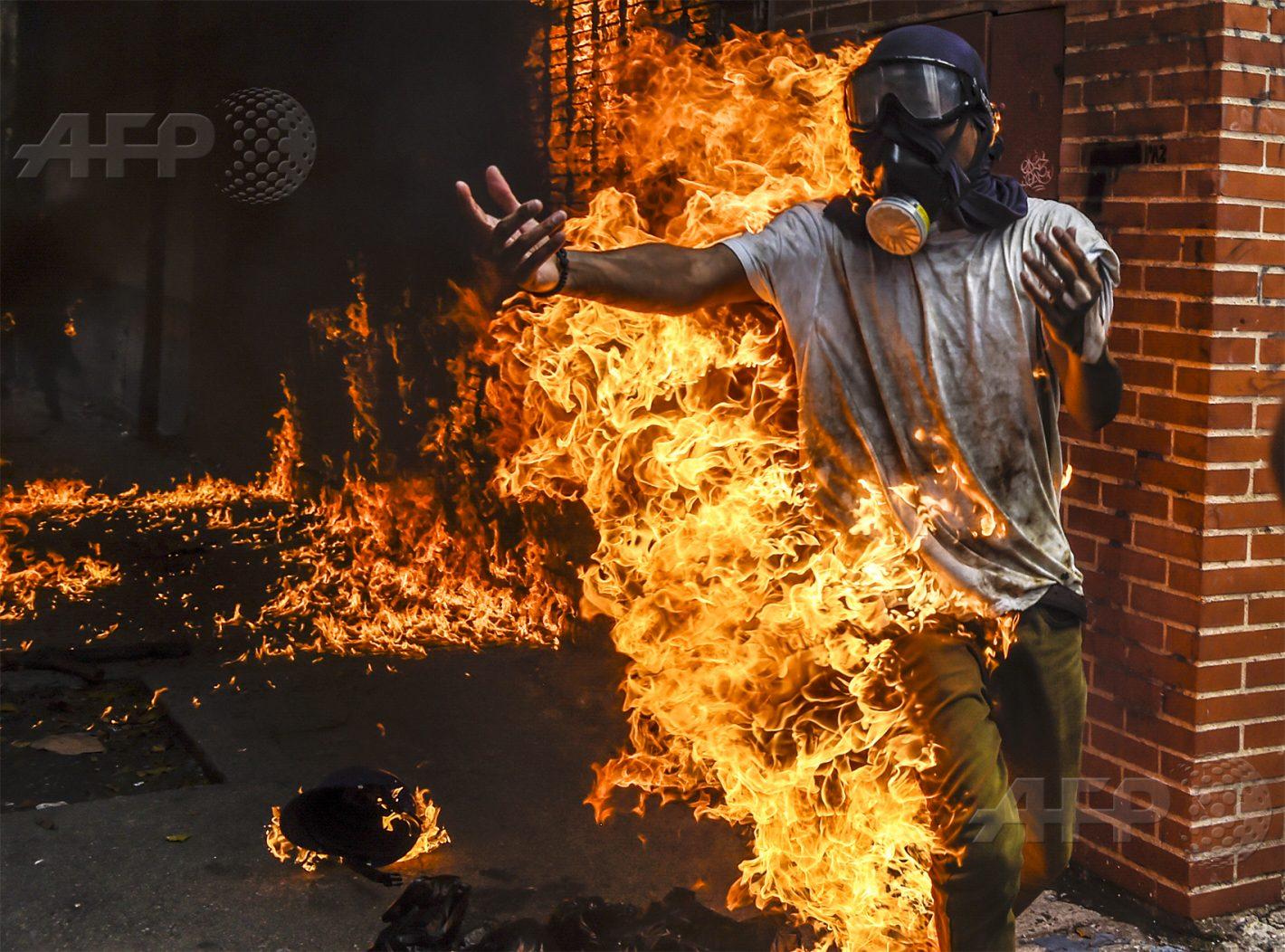 AFP 10 / VENEZUELA 3 mai 2017 - Caracas, Venezuela - Un manifestant prend feu après que le réservoir d'essence d'une moto de police a explosé, lors d'affrontements pour protester contre le président vénézuélien Nicolas Maduro. AFP / JUAN BARRETO