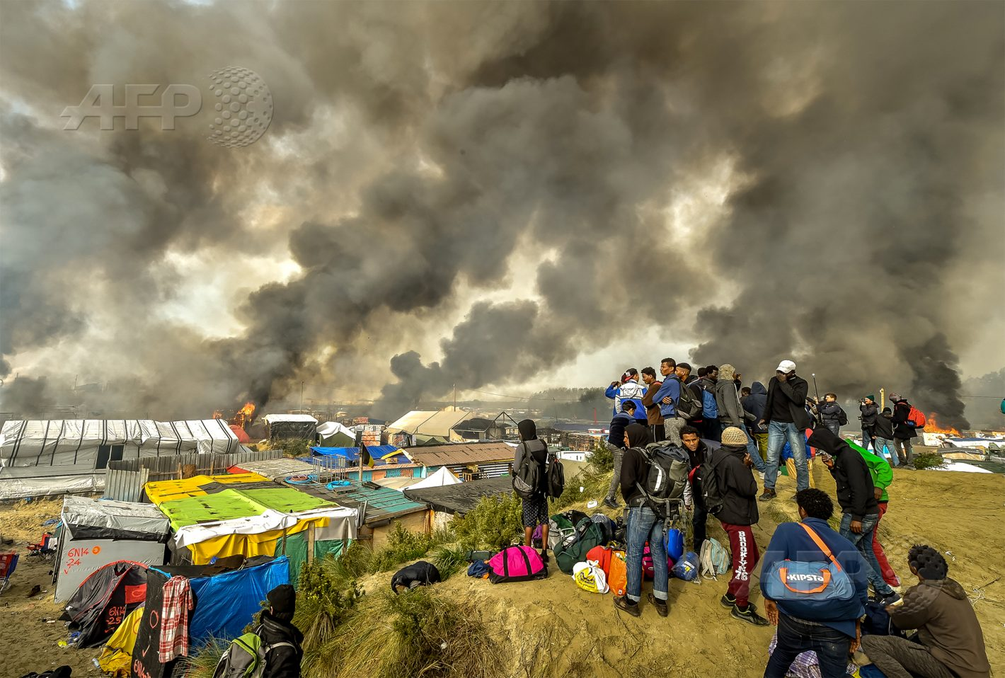 AFP 16 / FRANCE 26 octobre 2016 - Calais, France - Des migrants observent de multiples incendies volontaires dans la « Jungle » de Calais qui se sont déclarés dans la nuit, mobilisant pompiers et forces de l'ordre, au troisième jour de l'opération d'évacuation de migrants. AFP / PHILIPPE HUGUEN