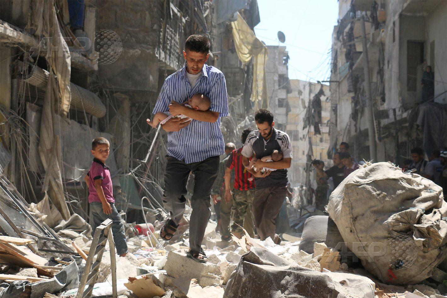 AFP 17 / SYRIE 9 juin 2016 - Alep, Syrie - Des casques blancs et des habitants évacuent des résidents dont l'immeuble a été touché par une attaque aux barils d'explosifs des forces du régime sur le quartier Al-Fardous tenu par les rebelles. AFP / AMEER ALHALBI