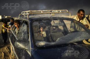 AFP 18 / IRAK 22 octobre 2016 - Qayyarah, Irak - Un père et ses deux enfants arrivent dans un centre pour réfugiés alors que plus de 10 000 Irakiens ont déjà fui leur foyer depuis le début de l'offensive terrestre qui a commencé le 17 octobre. L'épaisse fumée noire qui s'élève à l'horizon provient des champs de pétrole qui ont été incendiés par le groupe État Islamique. AFP / BULENT KILIC