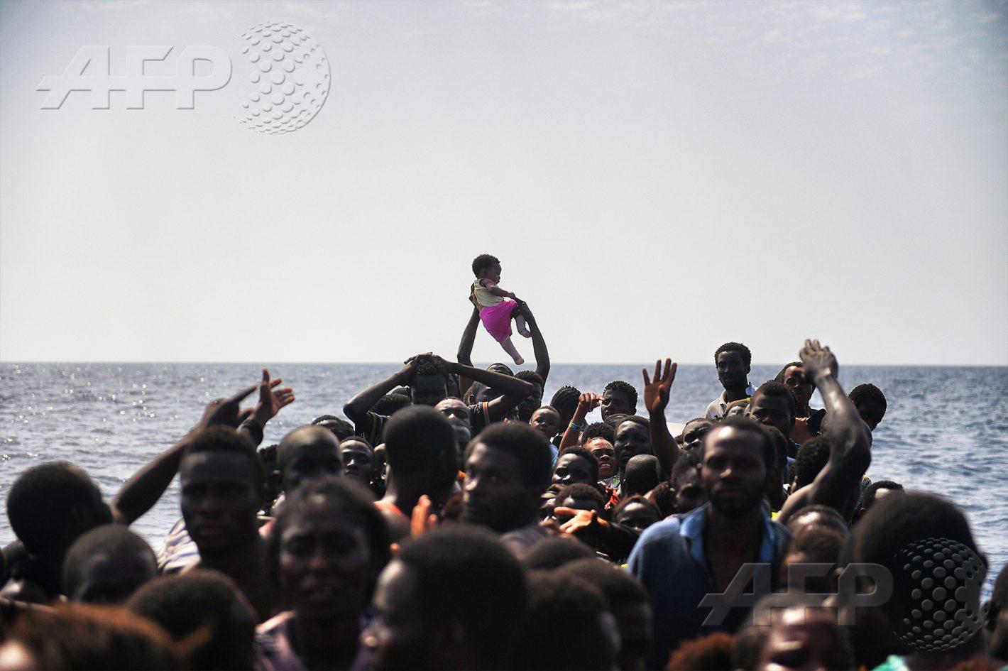 AFP 19 / LIBYE 4 octobre 2016 - Au large des côtes libyennes - Un enfant passe de main en main alors que les migrants attendent d'être secourus par des membres de l'ONG Proactiva Open Arms, à 12 milles nautiques (22,22 km) au nord de la Libye. AFP / ARIS MESSINIS