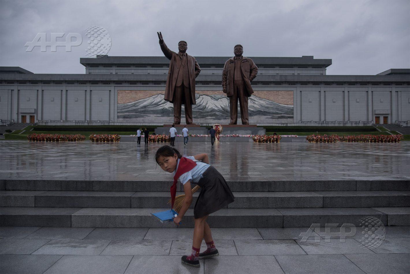 AFP 20 / CORÉE DU NORD 27 juillet 2017 - Pyongyang, Corée du Nord - Une jeune fille balaie les marches tandis que des visiteurs s'inclinent devant les statues de Kim Il-Sung (gauche) et Kim Jong-Il, alors que le pays célèbre le 64e anniversaire de la signature de l'armistice. AFP / ED JONES