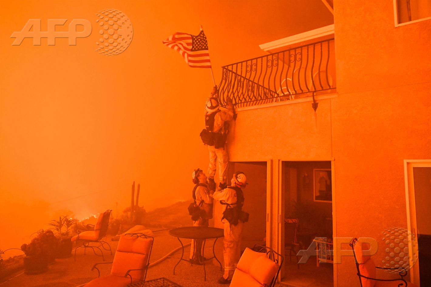 AFP 4 / ÉTATS-UNIS 8 juillet 2017 - Oroville, États-Unis - Des pompiers retirent un drapeau américain alors que des flammes du « mur de feu » se rapprochent d'une propriété. Les pompiers combattent plusieurs feux de forêt en Californie, qui a subi cinq longues années de sécheresse et qui connaît actuellement des températures particulièrement élevées. AFP / JOSH EDELSON