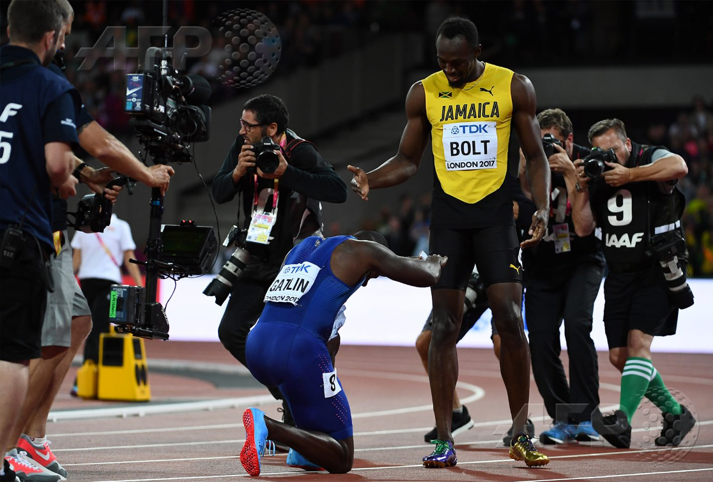 AFP 8 / ROYAUME-UNI 5 août 2017 - Londres, Royaume-Uni - L'Américain Justin Gatlin s'agenouille devant Usain Bolt après avoir remporté la finale du 100m aux Championnats du monde d'athlétisme. Bolt prend la troisième place. AFP / JEWEL SAMAD