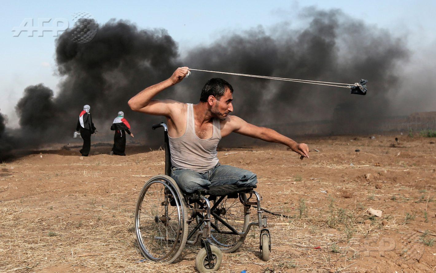 11 mai 2018 – bande de Gaza - Le Palestinien Saber al-Ashkar, 29 ans, lance des pierres durant des affrontements avec les forces israéliennes le long de la frontière, à l'est de la ville de Gaza AFP PHOTO / MAHMUD HAMS