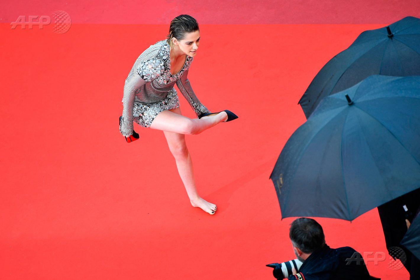 14 mai 2018 – Cannes - L'actrice américaine Kristen Stewart, membre du jury pour le meilleur long-métrage, retire ses chaussures à son arrivée pour la projection du film «BlacKkKlansman», lors de la 71ème édition du Festival de Cannes. AFP / Alberto PIZZOLI