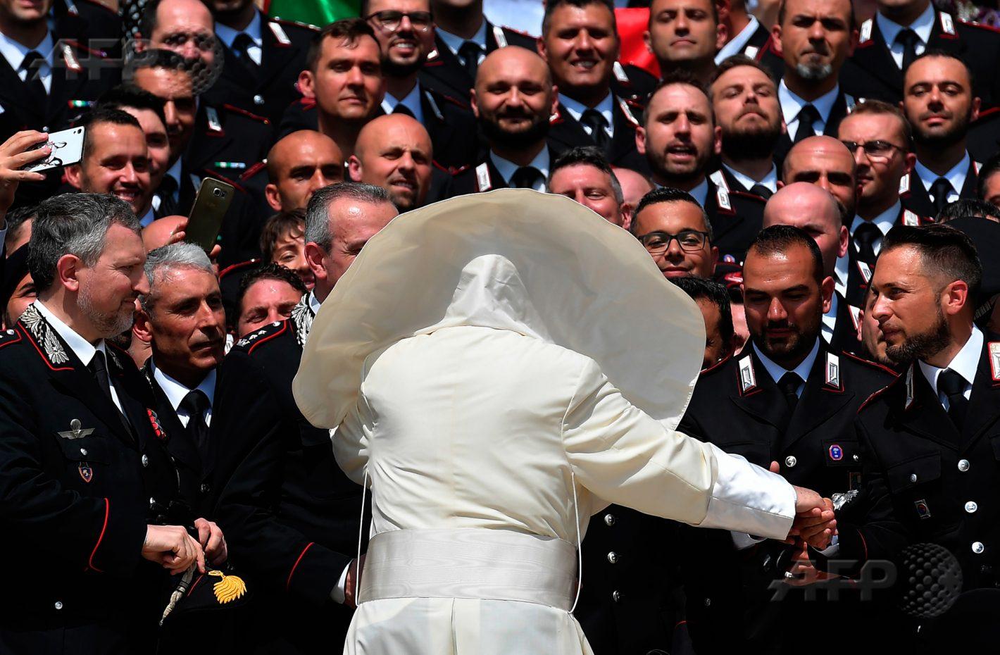 30 mai 2018 - Vatican - Une brise soulève le manteau du pape François lors d'une rencontre avec les Carabinieri durant l'audience générale sur la place Saint Pierre. AFP PHOTO / TIZIANA FABI