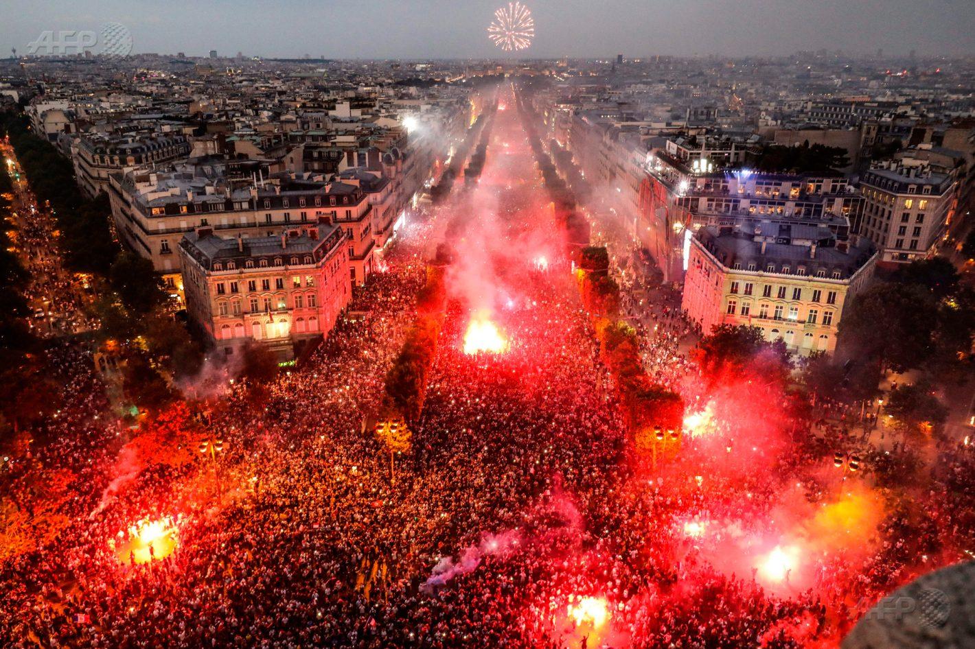 15 juillet 2018 – Paris – Vue générale réalisée depuis le sommet de l'Arc de Triomphe montrant la foule allumant des fumigènes sur les Champs-Elysées pour célébrer la victoire de la France face à la Croatie (4-2), lors de la finale de la Coupe du monde de football en Russie. AFP PHOTO / Ludovic MARIN