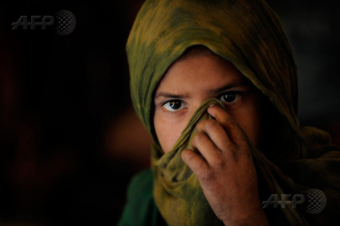 27 octobre 2010 – Kaboul - Une jeune fille de l'ethnie Kuchi se couvre le visage alors qu'elle assiste à un cours sous une tente devant les ruines du palais de Darulaman, détruit durant la guerre civile, en périphérie de la capitale. AFP PHOTO / SHAH MARAI