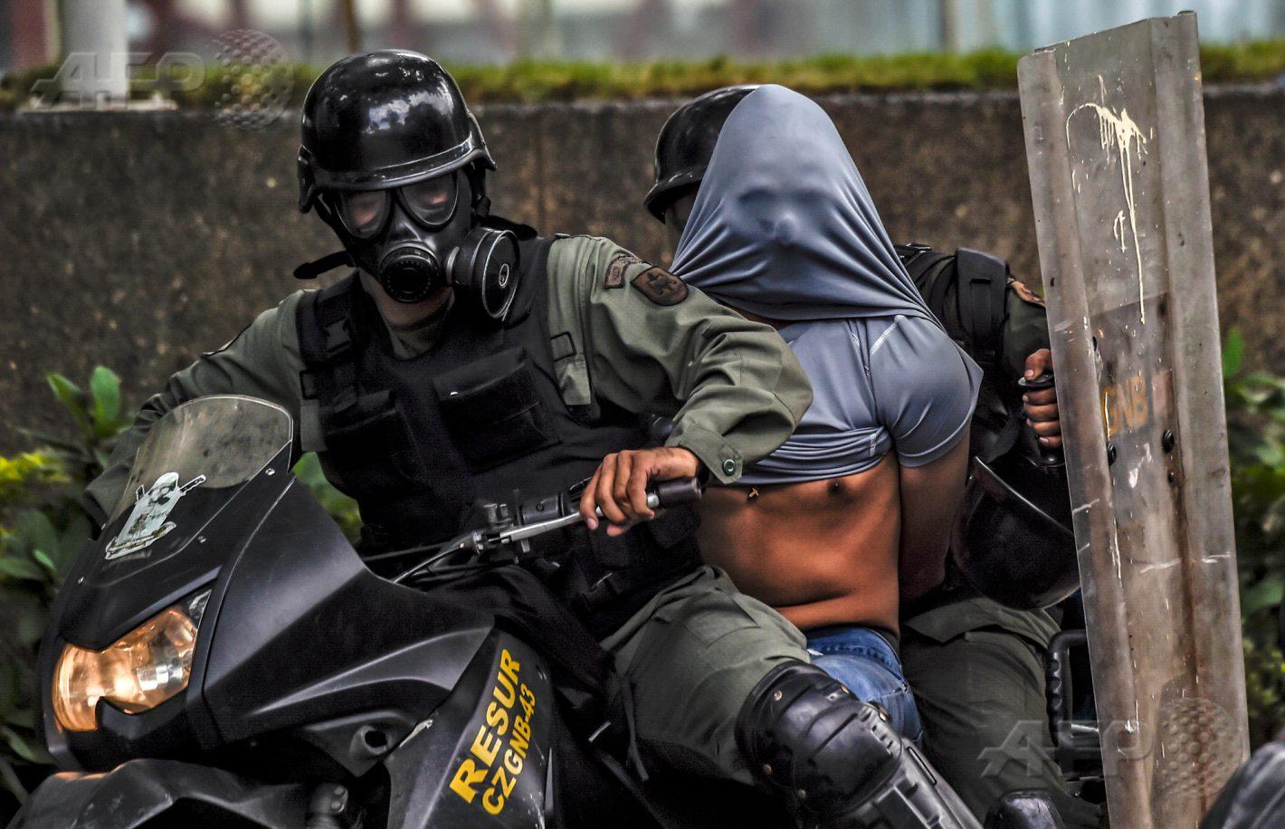 22 juillet 2017 – Caracas - La police anti-émeute arrête un activiste de l'opposition durant des affrontements lors d'une marche en direction de la cour suprême de justice conduite en opposition au président Maduro et son projet d'Assemblée constituante. AFP PHOTO / JUAN BARRETO