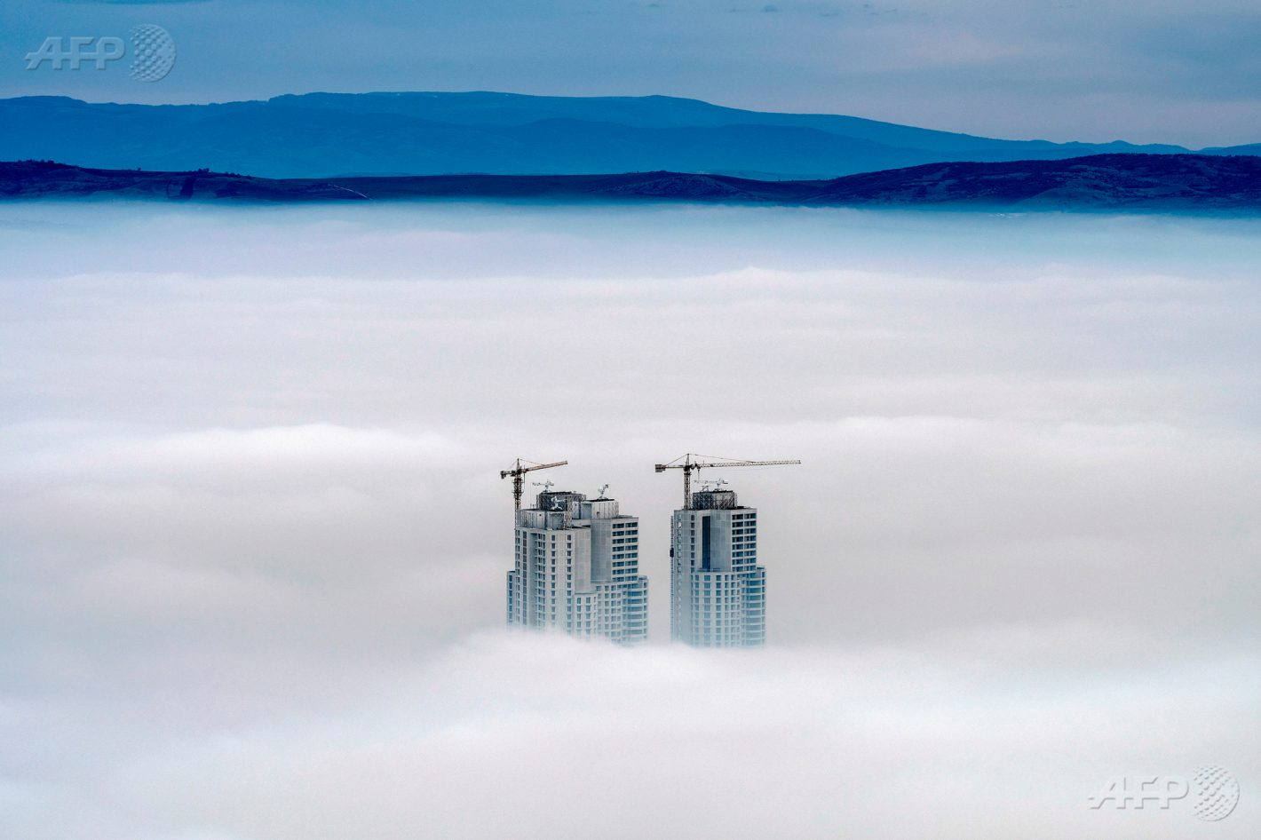 15 décembre 2017 - Skopje, Macédoine - Photo prise depuis le mont Vodno montrant le sommet d'immeubles émergeant des nuages, alors que la capitale macédonienne enregistre un fort taux de pollution. AFP PHOTO / Robert ATANASOVSKI