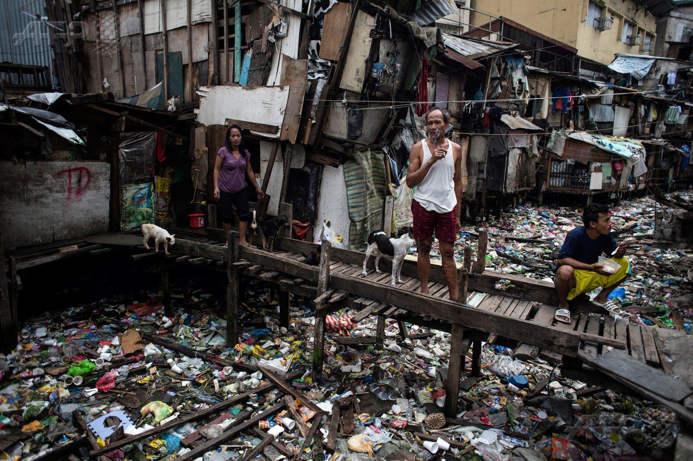 17 janvier 2018 – Manille - Des habitants se tiennent sur une passerelle surplombant un canal jonché de déchets. AFP PHOTO / NOEL CELIS