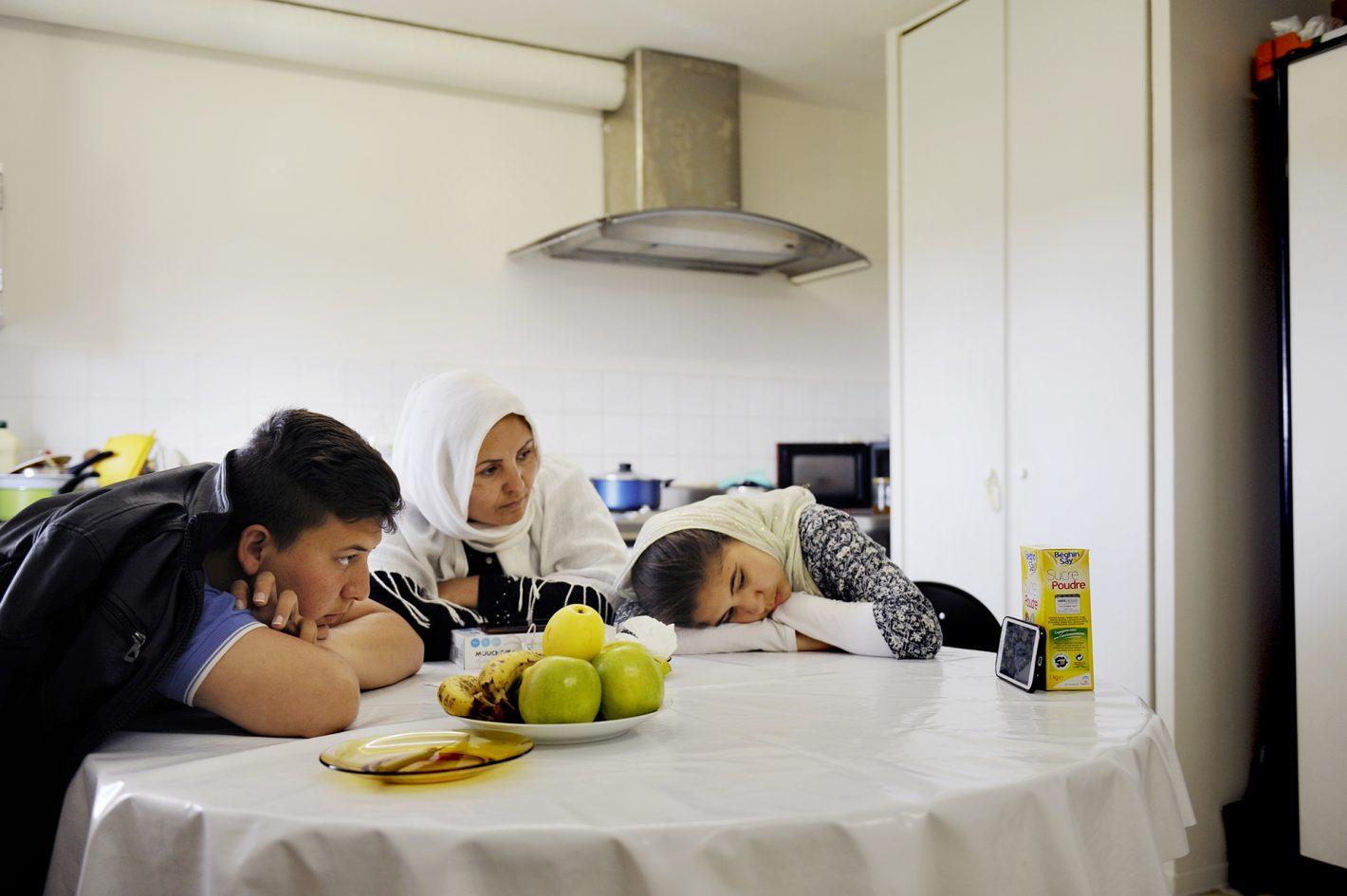 Pour tromper l'ennui, la famille regarde des séries sur le télépone portable d'Ali. La famille Sajadi : Seyed-Asghar le père, Rahima la mère, Ali 13 ans et Soraya 11 ans, vient d'Afghanistan. Membre de la minorité chiite Hazara du pays, cette famille a fui les talibans et est arrivée en France il y a six mois. Ils sont hébergés de manière provisoire dans ce centre situé en pleine zone rurale, à une heure de Toulouse. Le temps de préparer leur dossier pour l'OFPRA (l'Office Français de Protection des Réfugiés et Apatrides). Ce rendez-vous sera déterminant pour obtenir ou pas le statut de réfugiés. En 2015, seules 30% des demandes ont reçu une réponse positive. En attendant, chacun trompe l'ennui comme il peut. Soraya a intégré une classe de FLE (Français Langues Etrangères) dans l'école du village avec les autres enfants du CADA. Ses parents prennent également des cours de français au sein du CADA. Centre d'Accueil de Demandeurs d'Asile (CADA) Pierre Bayle, Carla-Bayle, Ariège, (09) 23 mai 2016.