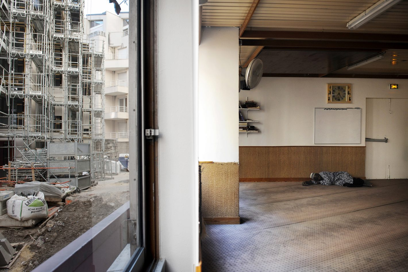 Salle de prière dans le foyer. Ce foyer doit fermer en décembre 2016. Par la fenêtre, on aperçoit la future Résidence Sociale en chantier qui accueillera une partie des résidents. Dans les résidences sociales, les espaces communs sont réduits au minimum voire supprimés. Il n'y aura plus de salle de prière, ce que déplorent les délégués du foyer Senghor. Ils essaient de négocier avec Adoma pour en avoir une. Foyer de Travailleurs Migrants Senghor, Paris 13ème, 7 juillet 2016.