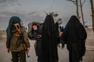 Women who are used to be IS (Islamic State) members and wives of IS members walk as a female fighter of SDF(Syrian Democratic Forces) fallow them closely as they travel in the Al Hol camp outskirts of Hasakah on February 17, 2019. AFP/BULENT KILIC